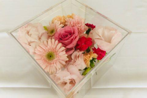 アクリルケースに納められたピンクの薔薇などの色とりどりの花々。