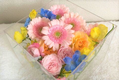アクリルケースに納められたピンクのガーベラなどの色とりどりの花々。