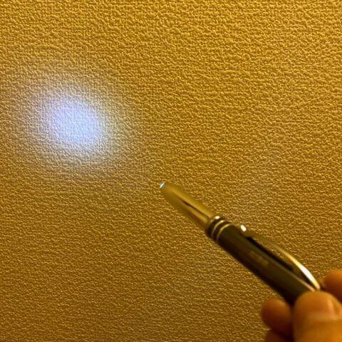 ペンのライトを壁に照らしている様子