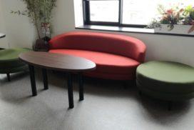 赤いソファと緑色のオットマンが置いてある待合室イメージ