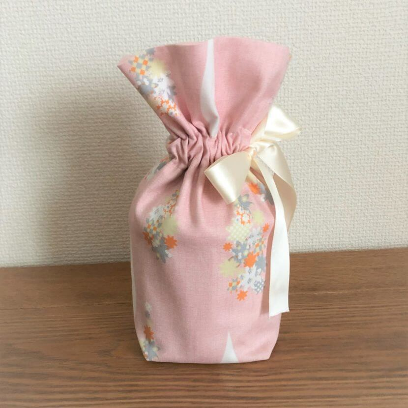 ピンク色の生地をベースに花柄のアクセントの付いたペット用のお骨袋