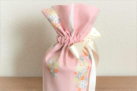 ピンク色の生地をベースに花柄のアクセントの付いた当社オリジナルのペット火葬用お骨袋